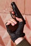 开枪在他的在一副黑手套的手 库存图片