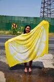 洗染黄色自然颜色的泰国妇女展示织品领带蜡染布 免版税库存图片