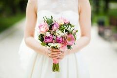 柔和的婚礼花束在新娘的手上 免版税图库摄影
