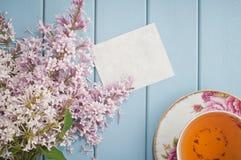 柔和的开花的丁香夏天花束与卡片和茶的 图库摄影