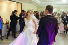 柔和的时髦的愉快的白肤金发的新娘和新郎第一个舞蹈  库存图片