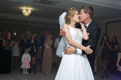 柔和的时髦的愉快的白肤金发的新娘和新郎第一个舞蹈  免版税库存图片