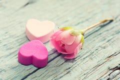 柔和的桃红色玫瑰和心脏在木桌上。 免版税库存图片