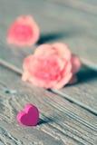 柔和的桃红色玫瑰和心脏在木桌上 免版税图库摄影