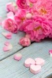 柔和的桃红色玫瑰和心脏在木桌上 免版税库存图片