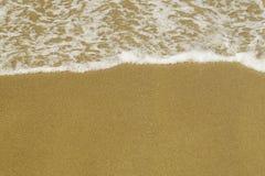柔和的泡影在美好的黄沙背景挥动 免版税库存照片