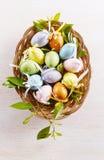 柔和的淡色彩上色了装饰在一块被编织的板材的复活节彩蛋 库存图片