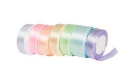 柔和的淡色彩在短管轴的色的缎丝带 免版税库存照片