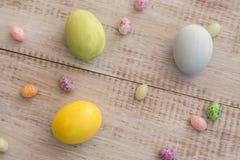 柔和的淡色彩色的复活节彩蛋和软心豆粒糖在白色木Backgro 免版税库存图片