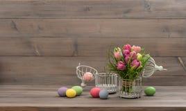 柔和的淡色彩色的郁金香花和复活节彩蛋 免版税库存照片