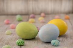 柔和的淡色彩被绘的复活节彩蛋和软心豆粒糖在木背景 库存图片
