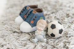 柔和的矮小的新生儿、足球和儿童的运动鞋 库存照片