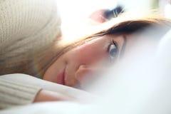 柔软在床上 放在板料之间的看妇女 免版税库存照片