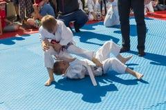 年轻柔道摔跤手在示范表现的8-10年 免版税图库摄影