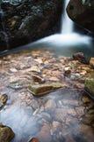 柔滑的缎软的瀑布在有岩石的森林里在长的曝光 库存照片