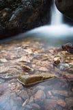 柔滑的缎软的瀑布在有岩石的森林里在长的曝光 图库摄影