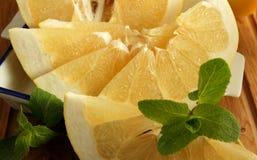 柚切片和薄菏在桌上 库存图片