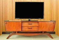 柚木树减速火箭的电视内阁在屋子里对木墙壁 免版税库存图片