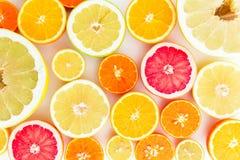 柠檬、桔子、葡萄柚、糖果和柚的柑桔样式 切的背景剪切果子半菠萝 平的位置,顶视图 免版税库存图片
