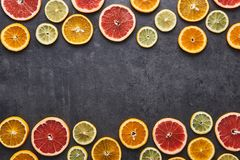 柠檬、桔子和葡萄柚的柑橘水果样式在黑石背景 库存图片