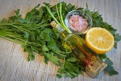 柠檬、橄榄油、新鲜的荷兰芹和喜马拉雅盐 免版税库存照片