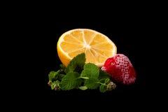 柠檬、结冰的草莓和薄菏在黑背景 查出 库存图片