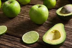 柠檬切片、鲕梨和绿色苹果在木桌上安排了 图库摄影