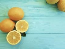 柠檬和桔子区分柠檬酸在蓝色木生气勃勃 库存图片