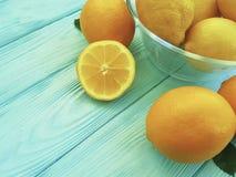 柠檬和桔子成熟在蓝色木 免版税图库摄影