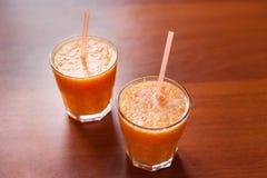 柠檬和橙色圆滑的人在桌上与切片柠檬和桔子在玻璃杯子有管的 免版税库存图片