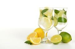 柠檬和石灰在一块玻璃用水在白色背景 库存图片