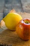 柠檬和苹果在一张粗砺的纹理桌上 免版税库存图片