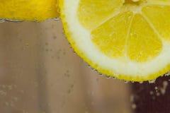 柠檬在与泡影的水中 免版税库存图片