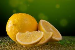 柠檬在水中在呈杂色的绿色背景滴下 库存照片