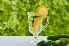 柠檬水在与冰和黄瓜切片的两块玻璃中在与拷贝空间的被弄脏的自然背景 r 图库摄影