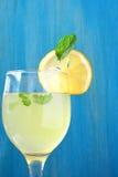 柠檬汁在玻璃和蓝色木背景中 库存图片