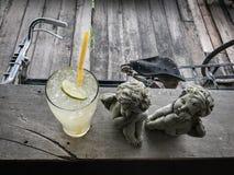 柠檬汁苏打和丘比特雕塑 免版税库存图片