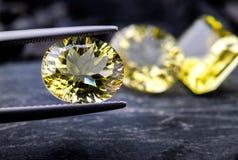 柠檬石英宝石首饰小组与黑石头和黑暗的照明设备的集合照片 库存照片