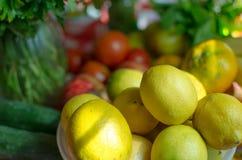 柠檬结果实聚光灯和黄瓜蕃茄和荷兰芹在背景 免版税图库摄影