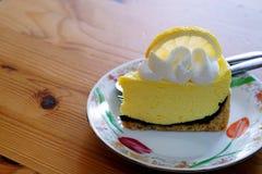 柠檬蛋白甜饼冠上了用在与拷贝空间的木桌安置的在白色板材和一个大新鲜的切片柠檬 图库摄影