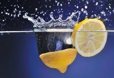 柠檬被投掷到水,行动,背景 免版税库存图片