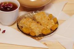 柠檬饼和金桔在板材说谎在一杯茶旁边 库存图片