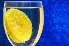 柠檬,盖用气体泡影在一块玻璃的在被弄脏的蓝色 免版税库存图片