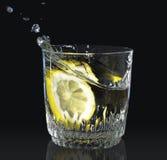 柠檬滴下了入一杯水 免版税库存照片
