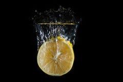 柠檬滴下了入水 免版税库存图片