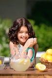 柠檬水摊的愉快的女孩 免版税库存照片