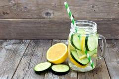 柠檬黄瓜在一个金属螺盖玻璃瓶的戒毒所水反对木头 免版税库存图片