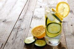 柠檬黄瓜在一块玻璃的戒毒所水在土气木头 免版税库存照片