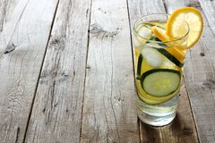 柠檬黄瓜在一块玻璃的戒毒所水在土气wooder土气木头 免版税库存图片