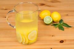柠檬水用两个柠檬、石灰和薄菏,木背景 图库摄影